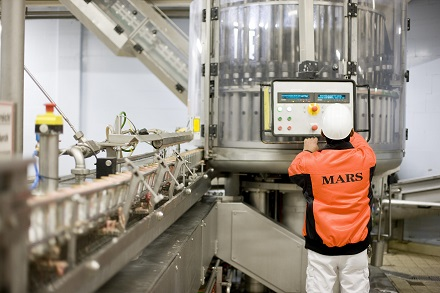 Mars associate in pet food factory operating a machine